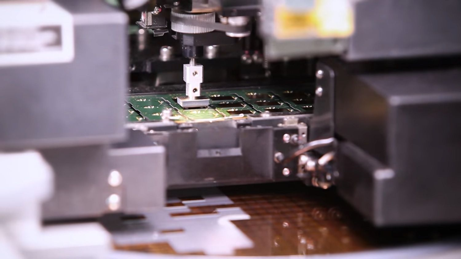 A machine picks a chip from the feeder and places it on to the PCB