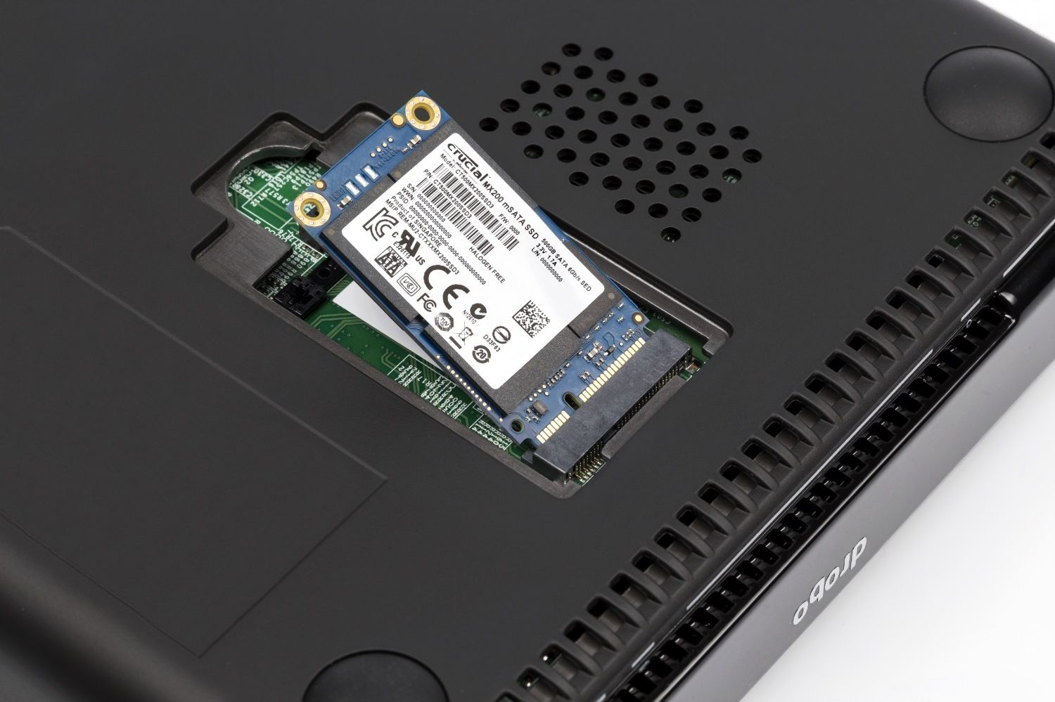 A Crucial MX200 MSATA SSD is being inserted in to a laptop