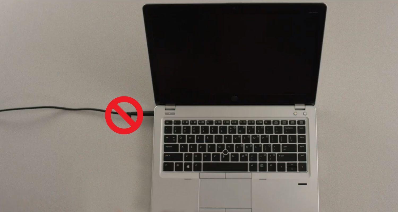 Un cercle barré placé sur le câble d'alimentation d'un ordinateur portable pour indiquer qu'il doit être retiré avant l'installation