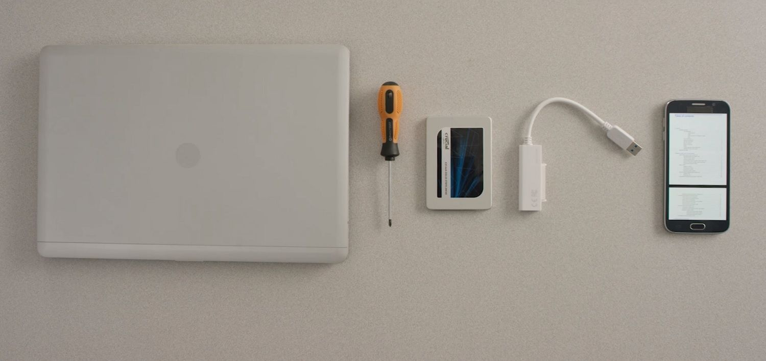 A laptop, Crucial SSD, screwdriver and computer's owner's manual on a mobile are laid out on a desk surface