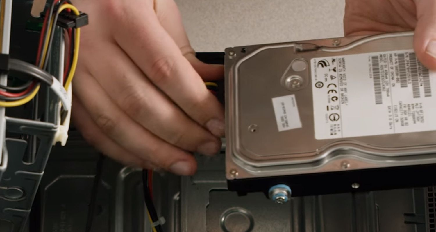 Person disconnecting cables from the storage drive of a desktop computer