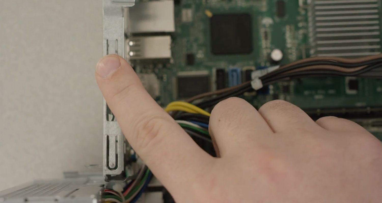 Fingerberührung einer unlackierten Metalloberfläche im Inneren eines Desktop-PCs zur Ableitung statischer Aufladung