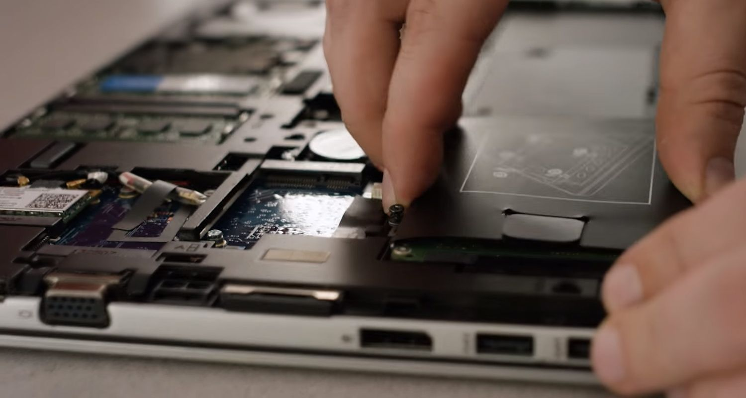 Crucial SSD being plugged in to the storage bay of a laptop