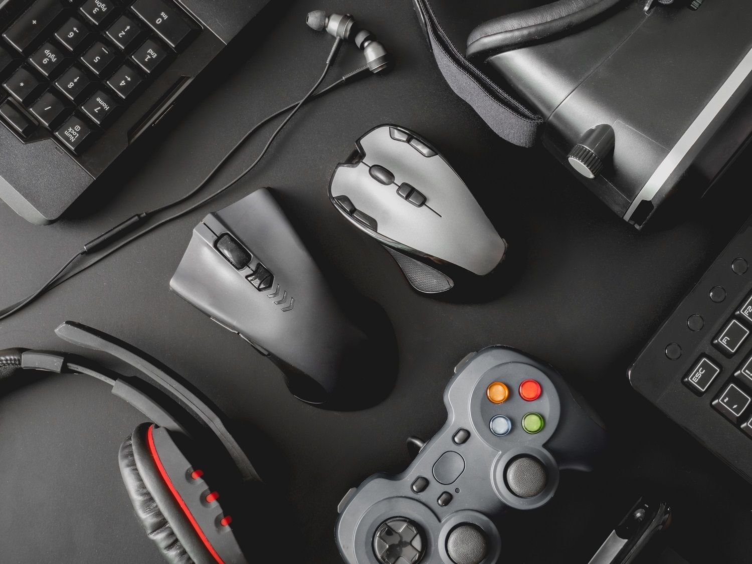 The peripherals of a gaming pc setup including a mouse, keyboard, gaming headphones, games controller and VR headset