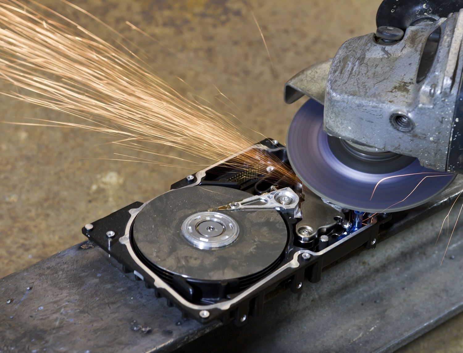 A hard disk drive is being destroyed by an electronic saw or grinder